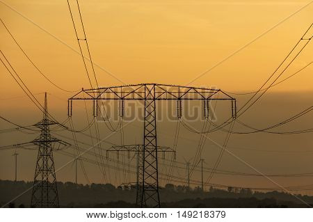 Electricity pylons and lines at dusk, Silhouette electricity pylons during sunrise. and wind power plant