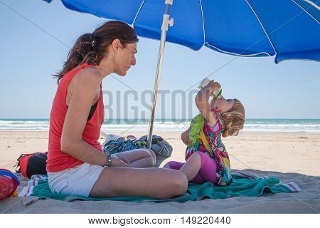two years old child with green bib drinking from blank beverage pack in hands with mother sitting down parasol umbrella at beach
