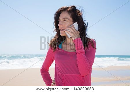portrait of brunette woman looking side with pink sweater smiling and listening to mobile phone smartphone at beach with sea and blue sky behind
