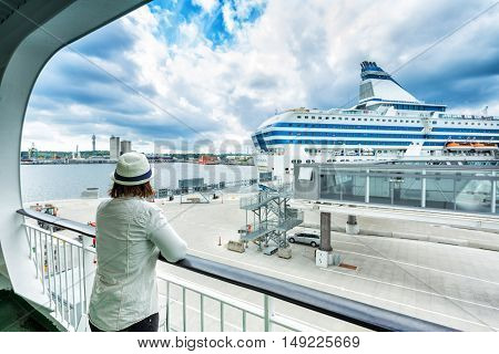 Woman relaxing on the ferry watching a cruiseship passing by