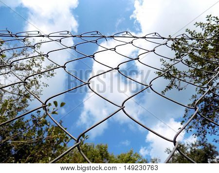 Chain link fence and partly cloudy sky