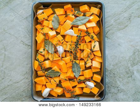 Chopped orange butternut squash on baking sheet with herbs/Diced Squash