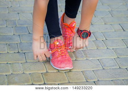 Young fitness girl ties up sneakers laces preparing for training working-out outdoor