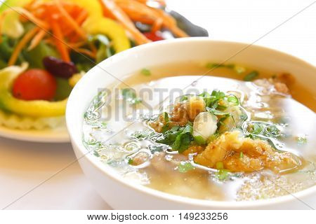 rice gruel or rice congee mixed with meat with the salad in a white bowl