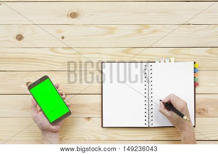 people holding and looking green screen display on smart phone with writing diary or notebook on top view wood table included clipping path on smartphone display