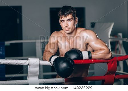 man in black boxing gloves on the ropes of the ring is worth. Recreation. Portrait of strong-willed person