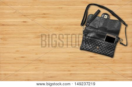 chic luxury leather black bag or wallet with smart phone on top view wood table business and fashion trend