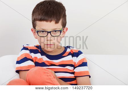 Portrait close up of cute serious kid little boy in glasses.