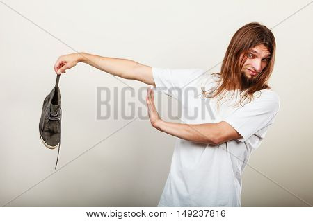 Young long haired man male wearing white t-shirt holding dirty stinky sweaty shoe in one hand fingers. Unpleasant smell stink.