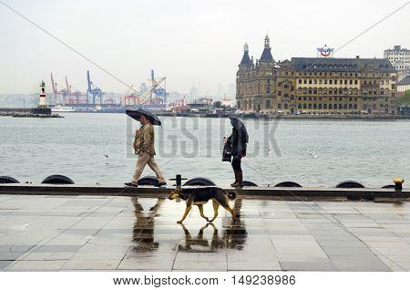 Istanbul, Turkey - April 18, 2014: Istanbul Kadikoy Steamboat pier and Haydarpasa train station building. People walking in the rain pier. Strait of Istanbul Kadikoy Pier ferries are the most popular form of public transport in Istanbul for.
