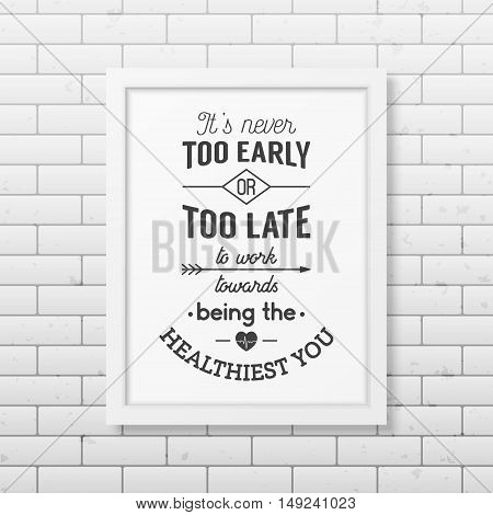 It is never too early or too late to work towards being the healthiest you - Typographical Poster in the realistic square black frame on the brick wall background. Vector EPS10 illustration.