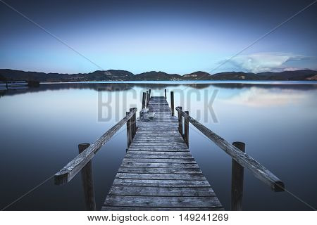Wooden pier or jetty on blue lake sunset and sky reflection water. Long exposure Versilia Massaciuccoli Tuscany Italy.