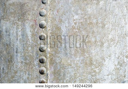 full background image of silver/brown sheet metal with a seam on one side with button like steel pegs down the side of the seam with room for text.