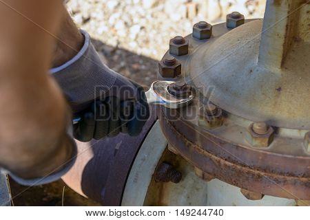 Workman looking to unlock the rusty valve.