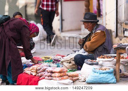 LEH LADAKH, INDIA - JULY 19, 2016 : Unidentified man in Market selling food material on walking street in Leh, India on Jul 19, 2016.