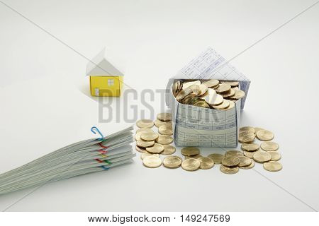 House of gold coins and pile overload document with colorful paperclip and little house on white background.