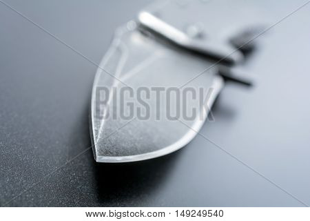 Macro Of A Knife Point Of An Opened Black Folding Knife Which Is Lying On Dark Ground