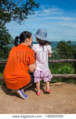 Happy asian family. Back view of mother and daughter enjoying at view point on mountain outdoor at the daytime on summer day. Travel on vacation.