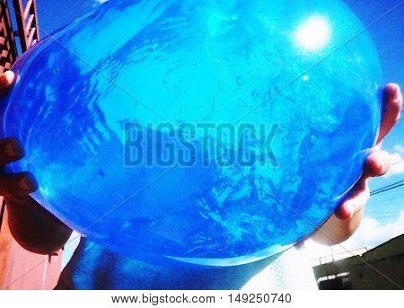 Balão com água azul, refletindo a luz do sol.