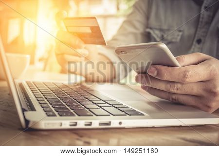Online paymentMan's hands holding smartphone and using credit card for online shopping with vintage filter effect