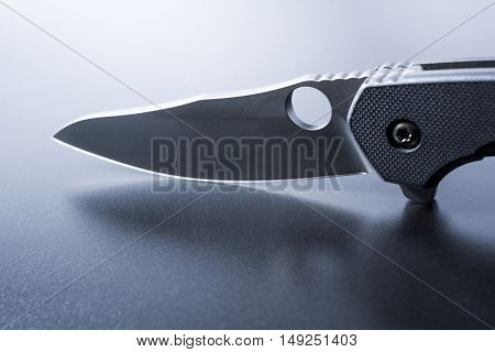 Macro Of A Blade Of An Opened Military Knife Which Stands On Dark Ground