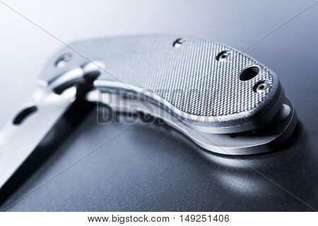 Close Up Of A Lying Half Opened Faint Military Knife On Dark Ground