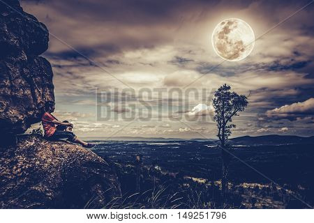 Woman Sitting On Boulders, Sky With Cloudy And Beautiful Full Moon, Outdoor At The Nighttime.