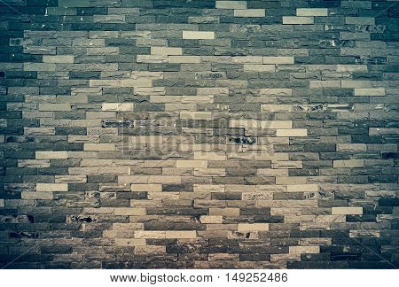 Old grunge brick wall background. Texture of stained old dark brick wall background horizontal architecture for your text. Cross process and vintage tone effect.