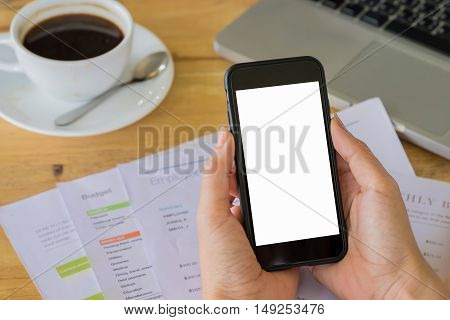 Hand holding smart phone and stock maket chart and laptop on wood desk. Smartphone with blank screen and can be add your texts or others on smart phone.Smart phone concept.