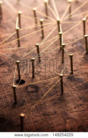 Linking entities. Network, networking, social media, internet communication abstract. A small network connected to a larger network. Web of gold wires on rustic wood. Shallow depth of field.