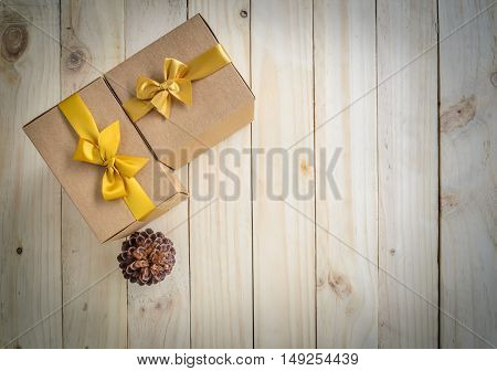 Christmas brown gift boxes with gold bow and pine cone on wooden background for copy space