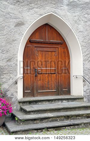 arched wooden church door with pink impatiens in flower pot