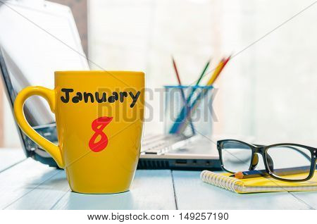 January 8th. Day 8 of month, Calendar on cup morning coffee or tea, financial adviser workplace background. Winter time. Empty space for text.
