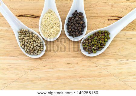 Green bean white sesame black and white pepper in white ceramic spoon on block wooden background