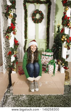 pretty happy smiling young teenage hipster girl infront of decorated for Christmas house, waiting for guests coming, winter snow around, lifestyle real people concept on holiday
