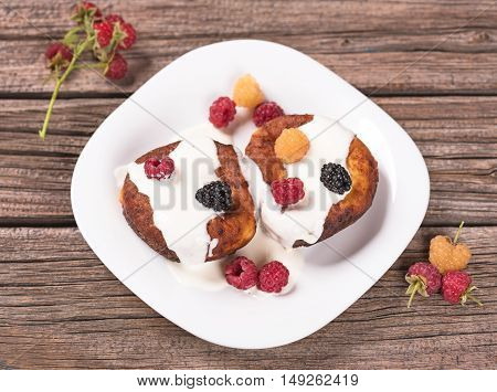 Delecious cheese-and-curd cake with fruits on the old wooden surface