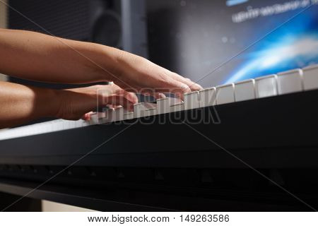 female's  hands playing piano