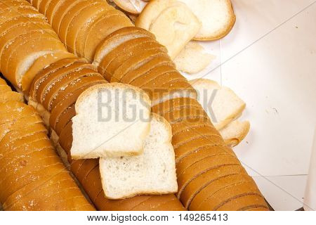 Breads petite white or sandwich placed in box paper. closeup. of a pile of mini toasts