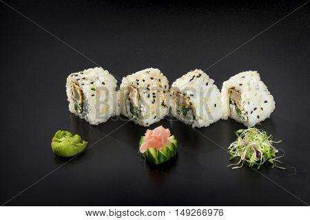 Uramaki maki sushi with sesame party Isolation on a black background
