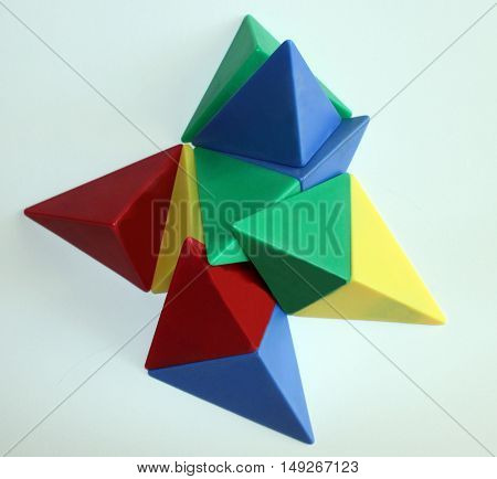 Polygon shapes placed in patterns with red, blue, yellow, and green 3-D pyramid triangular shapes isolated on white background.