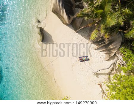 Aerial photo of Seychelles tropical beach Anse Source D Argent at La Digue island with young woman sunbathing