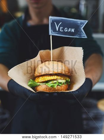 Fresh vegan snack - burger cooked at barbecue outdoors. Healthy bbq food with text label. Big hamburger with soy steak and vegetables closeup with chef unfocused at background. Street food, fast food.