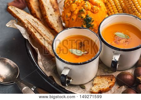 Pumpkin cream soup with sage and spices in a white vintage mugs. Autumn background