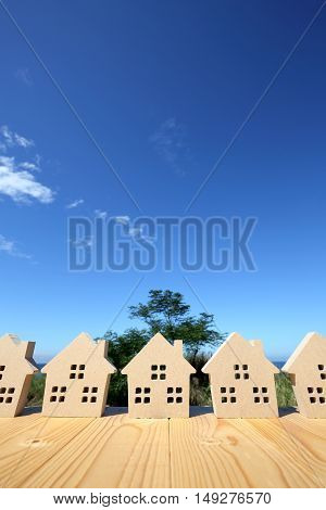 wooded toy house against clear blue sky background