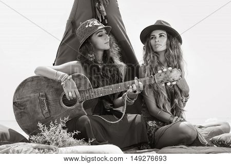 Two Beautiful Boho Girls With Guitar Sitting On Pillows At Tepee