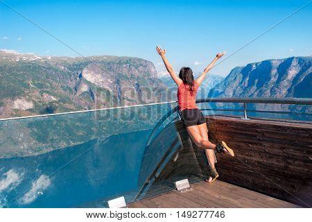 Joyful woman enjoying scenics from Stegastein Viewpoint in a summer sunny day , Flam, Norway
