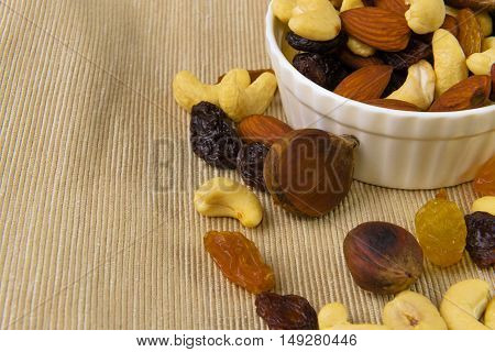raisins and nuts in a saucer on the background of canvas old style