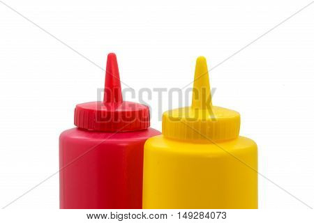 Top of a ketchup in the back and mustard bottle in the front closeup isolated on white