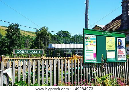 CORFE, UNITED KINGDOM - JULY 19, 2016 - Information board and sign at the railway station with a British Railways diesel Class 108 to the rear Corfe Dorset England UK Western Europe, July 19, 2016.