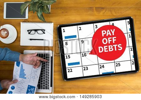 PAY OFF DEBTS Loan Money Bankruptcy Bill Businessman working at office desk and using computer and objects coffee top view poster